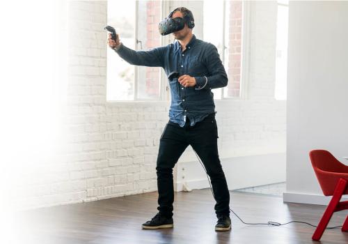 man using htc vive vr-system vr virtual reality immersinon 360° degrees game playing spielen training einarbeitung welten sicherheit